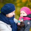 Mother and daughter at autumn park — Stock Photo
