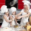 Mother and two daughters in the kitchen - Stock Photo