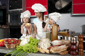 Mother and two daughters in the kitchen — Stock Photo