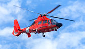 Red rescue helicopter moving in blue sky — Stock Photo