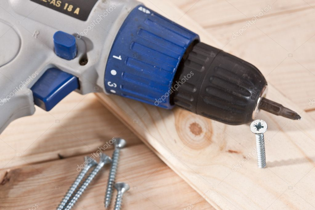 Tools series: long screw on wooden table with screwdriver — Stock Photo #5436392