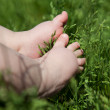 Baby foot on green grass — Stock Photo