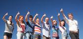 Raise hands across blue sky — Stock Photo