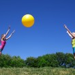 Two girls play with yellow ball — Stock Photo