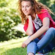Woman sitting on grass in park — Stock Photo