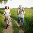 Stock Photo: Happy young couple riding on a bicycles