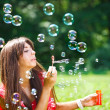 Stock Photo: Beautiful woman blowing soap bubbles