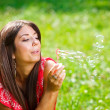 Beautiful woman blowing soap bubbles — Stock Photo