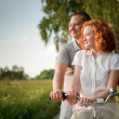 Young couple sitting one bicycle and looking at something — Stock Photo #6128618