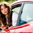 Young pretty woman looking at back of car — Stockfoto