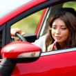 Woman doing makeup while driving - Stock Photo