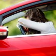 Stock Photo: Young woman sitting depressed in car