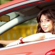 Young pretty woman in the red car — Stock fotografie #6315660
