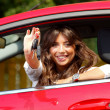 Beautiful young  woman in the new car with keys - Stock Photo