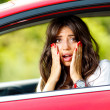 Young pretty woman in the red car - Stockfoto