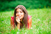 Beautiful woman lying on a grass — Stockfoto