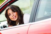 Jonge mooie vrouw kijken naar achterkant van auto — Stockfoto