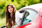 Young pretty woman looking at back of car — Stock Photo
