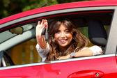Mooie jonge vrouw in de nieuwe auto met toetsen — Stockfoto