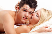 Loving affectionate heterosexual couple on bed. — Stock Photo