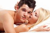 Loving affectionate heterosexual couple on bed. — Stock Photo