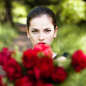 Woman with red lips giving flowers. — Stockfoto
