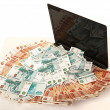 图库照片: Russibig pile of money on laptop