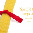 Bunch of spaghetti tied up with red ribbon isolated on white — Stock Photo