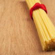 Bunch of spaghetti tied up with a red ribbon on a wooden backgro — Stock Photo