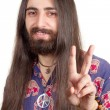 Friendly hippie with long hair making peace sign — Stock Photo #6001539