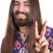 Friendly hippie with long hair making peace sign — Stock Photo #6001542