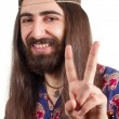 Friendly hippie with long hair making peace sign — Stock Photo #6001543