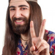 Stock Photo: Friendly hippie with long hair making peace sign