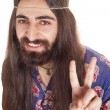 Friendly hippie with long hair making peace sign — Stock Photo #6001562