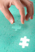 Hand inserting missing piece of green jigsaw puzzle into the hol — Stock Photo