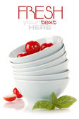 Stack of bowls and tomatoes — Stock Photo