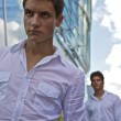 Two attractive man stay near modern business building — Stock Photo