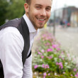 Young attractive man against beds with beautiful flowers. - Stok fotoraf