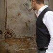 Handsome young man near an old metal door — Stock Photo #6523651