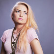 Blond girl in pink on studio gray background — Стоковая фотография