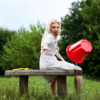 Emotional blonde does the drop by red bucket. Photo with motion. — Stock Photo