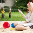 Beautiful young girl sits in a children's sandbox. — ストック写真