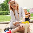 Beautiful young girl sits in a children's sandbox. — Stock Photo