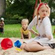 Beautiful young girl sits in a children's sandbox. — Stock Photo #6524093