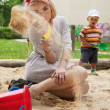 Beautiful young girl sits in a children's sandbox. — Stock Photo #6524097