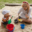 Beautiful young girl sits in a children's sandbox. — Stock Photo #6524102