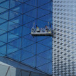 Workers washing the windows facade of a modern office building (cleaning gl - Zdjęcie stockowe