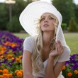 Portrait of beautiful blond woman in white retro hat siting near park — Stock Photo #6524403