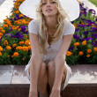 Portrait of beautiful blond woman in white retro hat siting near park — Stock Photo #6524409