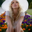 Portrait of beautiful blond woman in white retro hat siting near park — Stock Photo #6524414